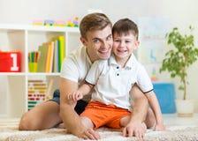Garçon d'enfant et son papa à la maison photographie stock libre de droits