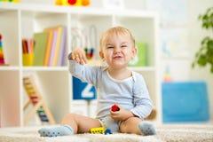 Garçon d'enfant jouant avec des jouets d'intérieur Image libre de droits