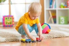 Garçon d'enfant jouant avec des jouets d'intérieur Photographie stock