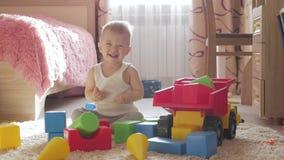 Garçon d'enfant jouant avec les blocs constitutifs se reposant sur le plancher à la maison Jeu d'enfant sur le plancher avec les  clips vidéos