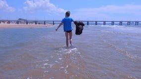 Garçon d'enfant sur des promenades de vacances de mer au repos d'eau de mer sur la plage sablonneuse dans le jour venteux banque de vidéos