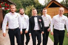 Garçon d'honneur élégant avec le marié se tenant sur l'arrière-cour et se préparer à la cérémonie l'épousant L'ami passent le tem photo stock