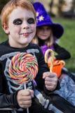 Garçon d'une chevelure rouge utilisant le costume squelettique de Halloween et tenant les sucreries colorées Image libre de droits