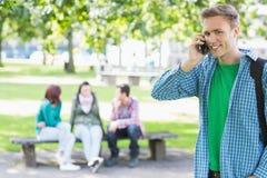 Garçon d'université à l'aide du téléphone portable avec des étudiants dans le parc Photos libres de droits