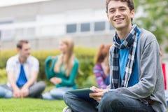 Garçon d'université de sourire à l'aide de la tablette avec des étudiants dans le parc Photographie stock libre de droits
