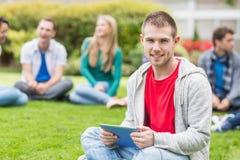 Garçon d'université de sourire tenant la tablette avec des étudiants en parc Image stock