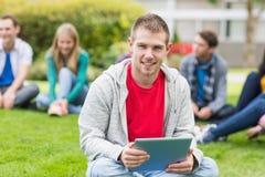 Garçon d'université de sourire tenant la tablette avec des étudiants en parc Photographie stock libre de droits