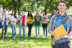 Garçon d'université tenant des livres avec des étudiants en parc Image stock