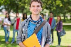 Garçon d'université tenant des livres avec des étudiants en parc Photos stock