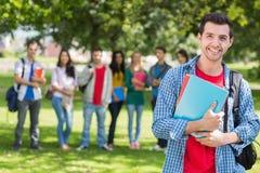 Garçon d'université tenant des livres avec les étudiants brouillés en parc Photos libres de droits
