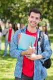 Garçon d'université tenant des livres avec les étudiants brouillés en parc Images libres de droits