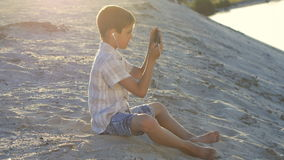 Garçon dans des écouteurs jouant des jeux sur le smartphone L'enfant de 10 ans apprécie un smartphone se reposant sur le sable au banque de vidéos