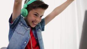 Garçon dans des écouteurs jouant le jeu vidéo sur l'ordinateur portable banque de vidéos