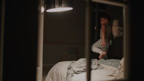 Garçon dans des pyjamas sautant sur le lit dans la chambre à coucher de sa maison Jeux riants avec un jouet banque de vidéos
