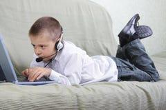 Garçon dans l'écouteur travaillant sur l'ordinateur portatif Photos libres de droits