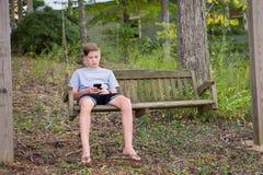 Garçon dans l'oscillation jouant ou textotant au téléphone Photos stock