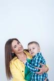Garçon dans la chemise se reposant avec la maman sur le fond clair Photographie stock