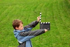 Garçon dans la jupe avec le panneau de clapet de cinéma photographie stock
