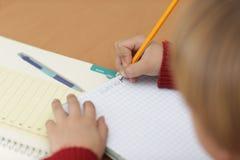 Garçon dans la salle de classe apprenant et dans le moment concertrated Images stock