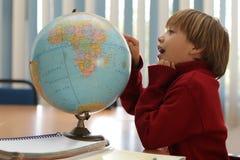 Garçon dans la salle de classe apprenant et dans le moment concertrated Image libre de droits