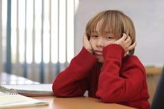 Garçon dans la salle de classe apprenant et dans le moment concertrated Photographie stock libre de droits