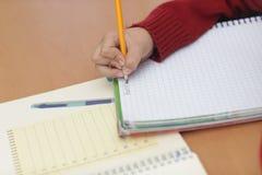 Garçon dans la salle de classe apprenant et dans le moment concertrated Image stock