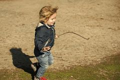 Garçon dans la veste bleue et la course heureuse de jeans avec le bâton photo stock
