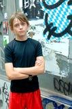 Garçon dans la ville par le mur de graffiti Image libre de droits