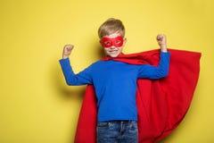 Garçon dans le cap et le masque rouges de superhéros surhomme Portrait de studio au-dessus de fond jaune Images stock