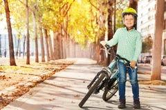 Garçon dans le casque se tenant avec le vélo au parc d'automne Photo libre de droits