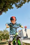 Garçon dans le casque se tenant avec le vélo au parc d'automne Photos stock