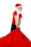Garçon dans le chapeau du père noël avec le sac de cadeau de Noël Image libre de droits