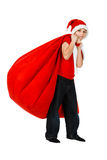 Garçon dans le chapeau du père noël avec le sac rouge de cadeau Image stock