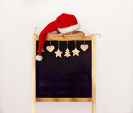 Garçon dans le chapeau du ` s de Santa avec le tableau noir décoré Photographie stock libre de droits