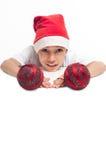 Garçon dans le chapeau rouge de Noël retenant les billes rouges Photos stock