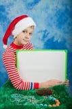 Garçon dans le costume de Noël tenant le carton blanc Photographie stock libre de droits