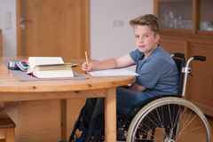 Garçon dans le fauteuil roulant faisant le travail Image stock