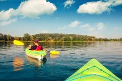 Garçon dans le gilet de sauvetage sur le kayak vert Photographie stock libre de droits