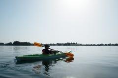Garçon dans le gilet de sauvetage sur le kayak vert Photo stock