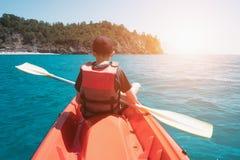 Garçon dans le gilet de sauvetage sur le kayak orange Images libres de droits