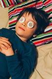 Garçon dans le lit avec les corrections idiotes d'oeil Photo libre de droits