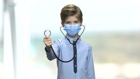 Garçon dans le masque protecteur utilisant le stéthoscope banque de vidéos