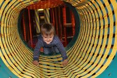 Garçon dans le tunnel sur la cour de jeu images stock