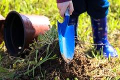 Garçon dans les bottes creusant dans la terre avec une pelle sur le TU Bishvat photos stock