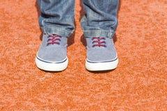 Garçon dans les espadrilles bleues et des jeans se tenant sur le fond rouge de terrain de jeu Fermez-vous vers le haut du tir de  Photos stock