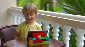 Garçon dans les tropiques parlant avec les amis et la famille à l'appel visuel utilisant un comprimé et des écouteurs sans fil clips vidéos