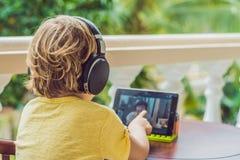 Garçon dans les tropiques parlant avec les amis et la famille à l'appel visuel utilisant un comprimé et des écouteurs sans fil Photographie stock libre de droits
