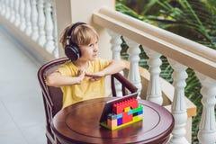 Garçon dans les tropiques parlant avec les amis et la famille à l'appel visuel utilisant un comprimé et des écouteurs sans fil Images libres de droits