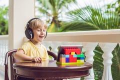 Garçon dans les tropiques parlant avec les amis et la famille à l'appel visuel utilisant un comprimé et des écouteurs sans fil Image libre de droits