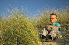 Garçon dans penser de dunes Images stock